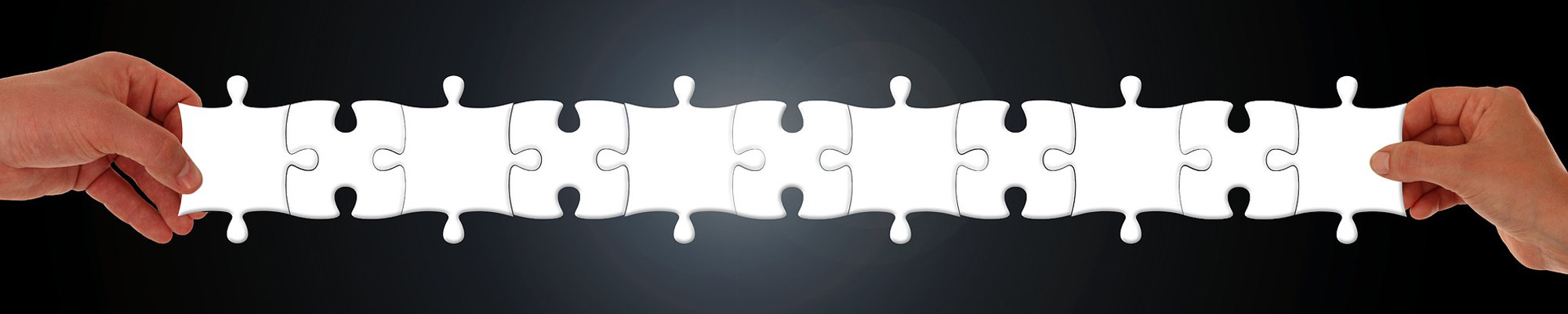 two hands holding linked puzzle pieces