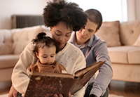 family of mixed race reading book to child