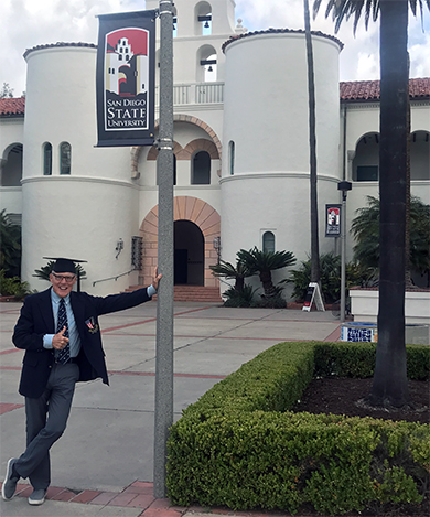 Jim Dieker in front Hepner Hall with graduation cap